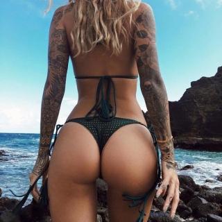 Фотография Пошлая атмосфера: Девушка с татуировками в купальнике стоит возле моря.