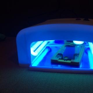 Фотография Мастер: Переклейка модуля на iPhone. Переклеенный модуль помещен в ультрафиолетовую камеру для того, чтобы клей застыл.
